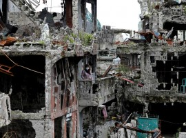 A woman stands at her ruined house, after residents were allowed to return to their homes for the first time since the battle between government troops and Islamic State militants began on May 2017, at the Islamic city of Marawi, Philippines April 19, 2018.
