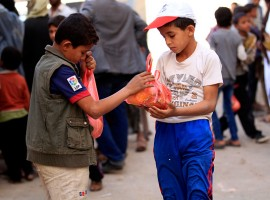 Yemeni children receive free food rations among five hundred families, recipients of an initiative by local youths during the holy month of Ramadan in the capital Sanaa on May 27, 2018.