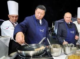 Russian President Vladimir Putin and Chinese President Xi Jinping make pancakes