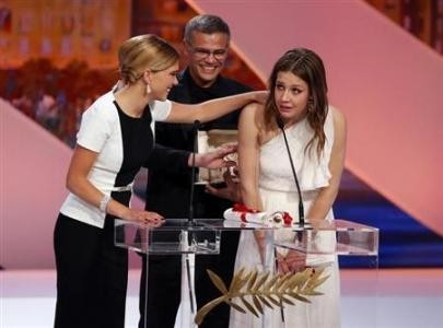 "Director Abdellatif Kechiche (C), actresses Lea Seydoux (L) and Adele Exarchopoulos (R), react on stage after he received the Palme d'Or award for the film ""La Vie D'Adele"" during the closing ceremony of the 66th Cannes Film Festival i"