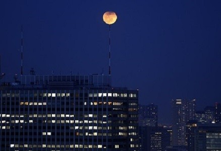 The partial lunar eclipse is seen atop an antenna installed on the roof of a high-rise building in Tokyo (Reuters)