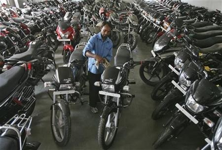A worker cleans a Hero Splendor motorcycle at a Hero MotoCorp showroom in Jammu October 23, 2012.