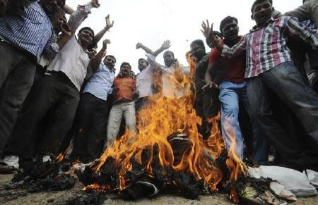 Pro-Telangana supporters shout slogans beside a burning effigy representing members of parliament from the state who have not submitted their resignations, during a strike in Hyderabad July 5, 2011.