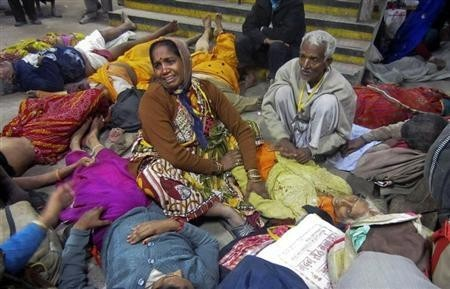 A woman cries as she sits among the bodies of people who were killed when part of a railing from a bridge collapsed at Allahabad railway station February 10, 2013.