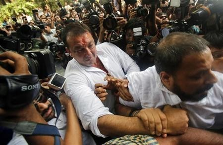 Bollywood actor Sanjay Dutt is escorted by his security staff as he arrives to surrender at a court in Mumbai May 16, 2013.