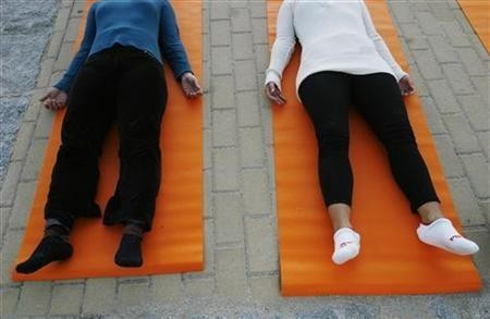 People take part in a free yoga class at the Parque del Oeste in Madrid September 27, 2007.