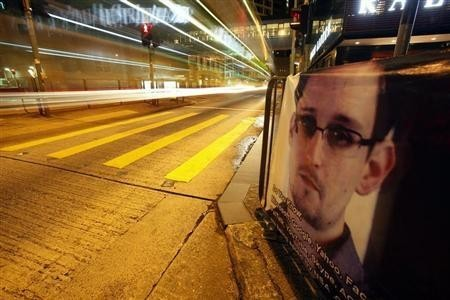 A bus passes by a poster of Edward Snowden, a former contractor at the National Security Agency (NSA), displayed by his supporters at Hong Kong's financial Central district.