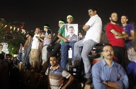 A supporter of Egypt's deposed President Mohamed Mursi holds a poster of him (C) while waiting with others as prayers are performed, during their sit-in outside the Rabaa Adawiya mosque, east of Cairo July 11, 2013.