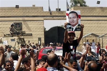 A supporter holds a poster of Hosni Mubarak outside Tora prison