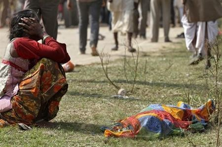 A woman cries next to a body of victim killed during Madhya Pradesh temple stampede