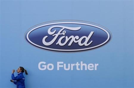A woman has a drink as she walks past a logo of carmaker Ford at the entrance to a media event for the launch of a concept car in Sydney August 13, 2013.