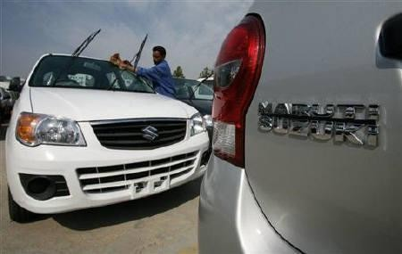 A worker cleans a parked car at the Maruti Suzuki's stockyard on the outskirts of Jammu October 30, 2010.