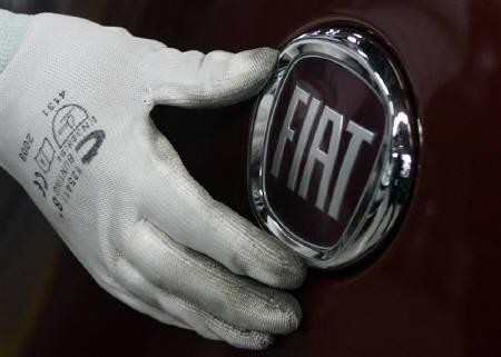A worker adjusts the logo on a new Fiat Punto at a Fiat factory assembly line in the central Serbian town of Kragujevac