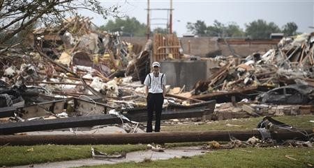 A man stands among the wreckage after a tornado struck Moore, Oklahoma, May 20, 2013.  REUTERS/Gene Blevins