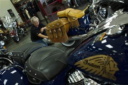 A worker cleans an Indian motorcycle before moving it to the showroom at Indian Motorcycles of Northern New Jersey in Union, August 20, 2013