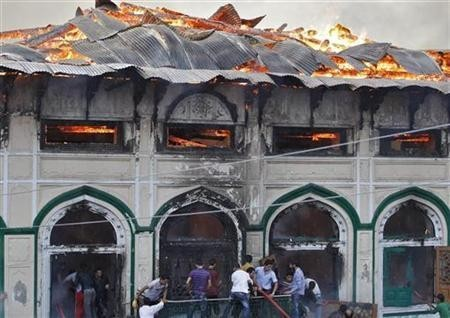 Local residents try to extinguish a fire that broke out at a Sufi shrine in Srinagar June 25, 2012. REUTERS/Danish Ismail