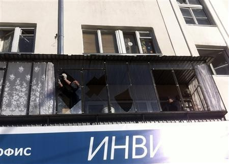 A man removes shards of glass from the frame of a broken window following sightings of a falling object in the sky in the Urals city of Chelyabinsk February 15, 2013.