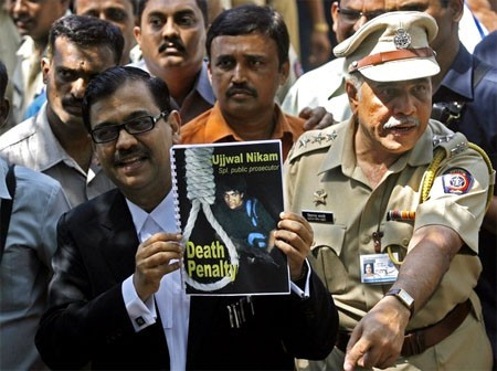 Special Prosecuter Ujjwal Nikam holds up a document, with a cover showing Mohammad Ajmal Kasab, at Arthur Road Jail, where Kasab's trial was held, in Mumbai May 6, 2010