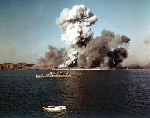 Smoke rises over Hungnam's port area, as facilties and remaining U.N. supplies are demolished by explosives on the final day of evacuation operations during Korean War, December 24, 1950.