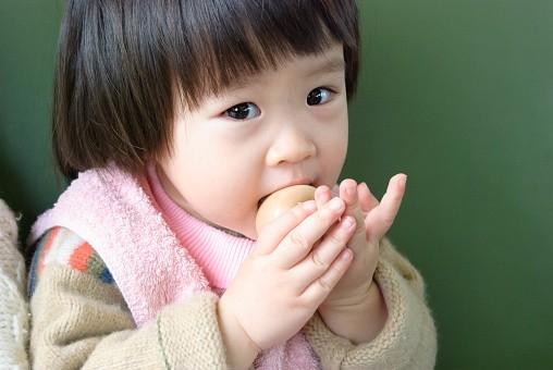 Baby eating egg