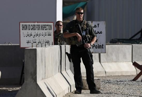 Afghan and foreign security personnel stand guard at the site of a blast, outside the counter-narcotics office near the Kabul International Airport