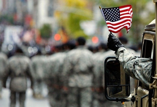A U.S. Armed serviceman waves an American flag along 5th Avenue during the Veterans Day parade /Reuters File