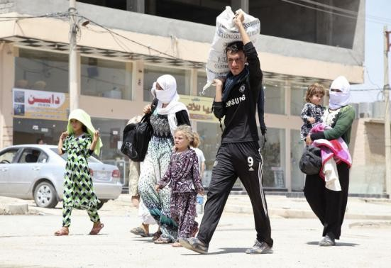 Displaced families from the minority Yazidi sect, fleeing the violence in the Iraqi town of Sinjarl west of Mosul, arrive at Dohuk province, August 4