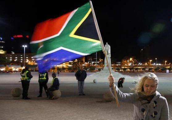 girl holds a South African national flag outside Cape Town City Hall, where Mandela made his first speech after his release from his 27year incarceration, December 6.
