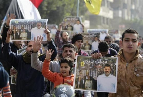 Supporters of the Muslim Brotherhood and ousted Egyptian President Mohamed Mursi protest against the military and interior ministry, while making the four-finger Rabaa gesture, at Nasr City district
