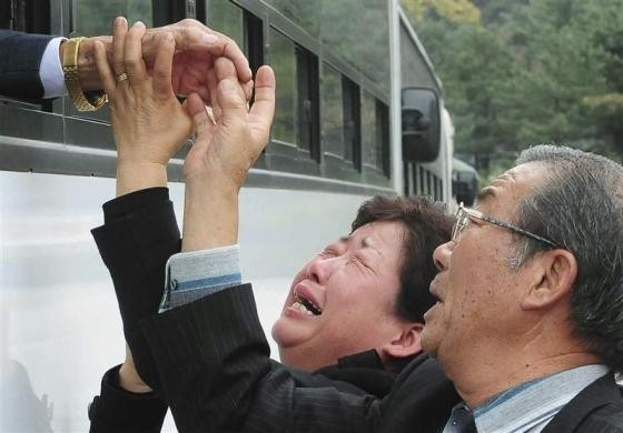 A North Korean man (L) waves from a bus as his South Korean relatives weep after a luncheon meeting during inter-Korean temporary family reunions at Mount Kumgang resort October 31, 2010.