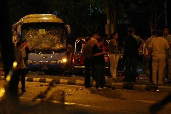 Officials stand around a bus with a smashed windshield following a riot in Singapore's Little India district, December 9, 2013.