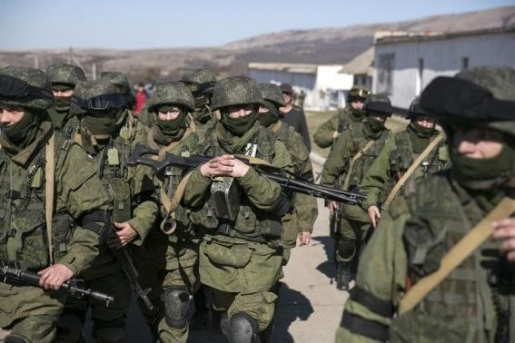 Military personnel, believed to be Russian servicemen, walk outside the territory of a Ukrainian military unit in the village of Perevalnoye outside Simferopol.