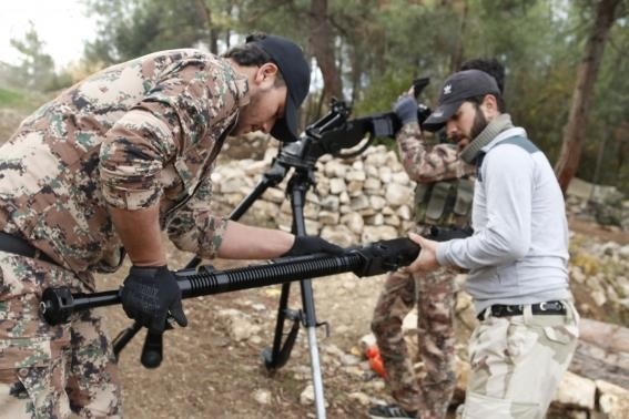 Rebel fighters prepare to fire a machine gun towards forces loyal to Syria's President Bashar al-Assad in the Jabal al-Akrad area in Syria's northwestern Latakia province November 25, 2014