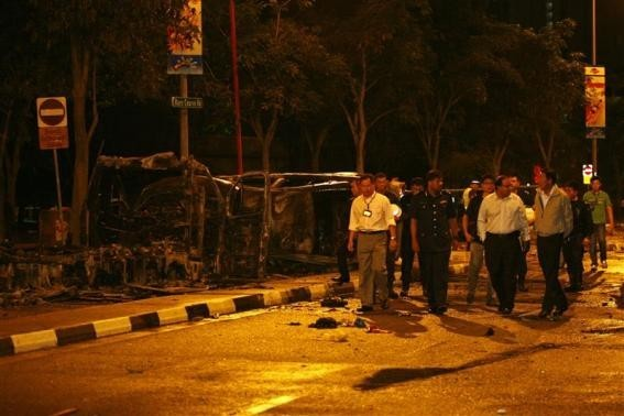 Singapore's Deputy Prime Minister Teo Chee Hean (front R) and Minister in Prime Minister's Office S Iswaran (front 2nd R) look at the site of two burnt vehicles following a riot in Singapore's Little
