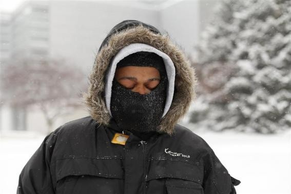 A man waits for a transit bus in several inches of snow in Detroit, Michigan January 2, 2014.