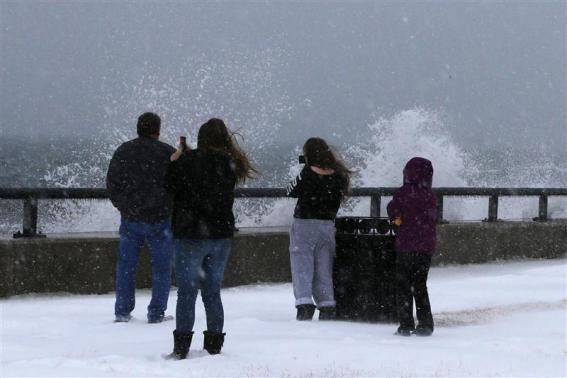 Onlookers look at waves crashing against the seawall around high tide during a winter nor'easter snowstorm in Lynn, Massachusetts January 2, 2014.