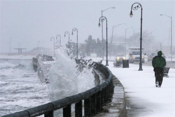 A man jogs past waves crashing against the seawall around high tide during a winter nor'easter snowstorm in Lynn, Massachusetts January 2, 2014.