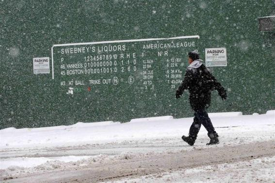 A pedestrian walks past a replica of the Fenway Park scoreboard during a winter nor'easter snow storm in Lawrence, Massachusetts January 2, 2014.
