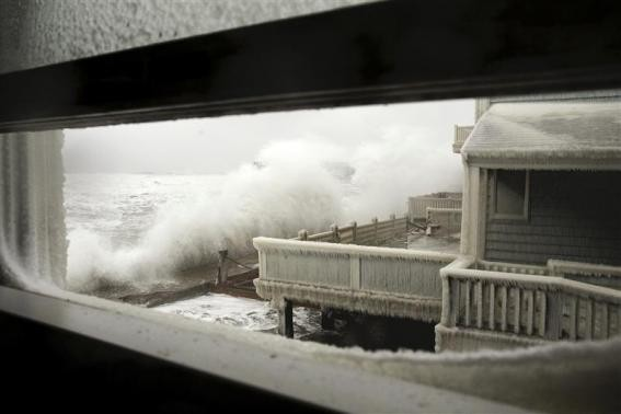 Waves crash into houses on Lighthouse Road during a winter nor'easter snow storm in Scituate, Massachusetts January 3, 2014.