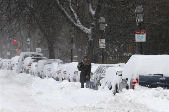 A driver works to dig a car out of the snow during a winter nor'easter snow storm in Boston, Massachusetts January 3, 2014.