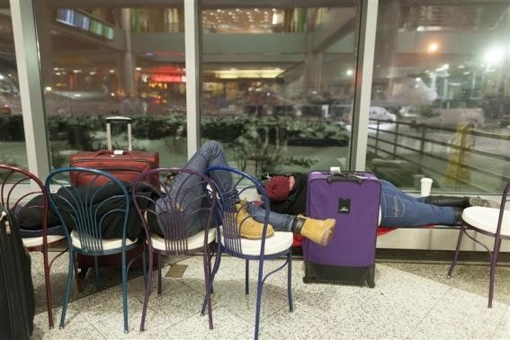 People wait for their delayed flights at LaGuardia Airport in New York January 3, 2014.