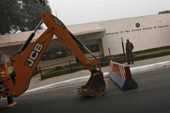 policeman stands next to a bulldozer removing the security barriers in front of the U.S. embassy in New Delhi December 17, 2013