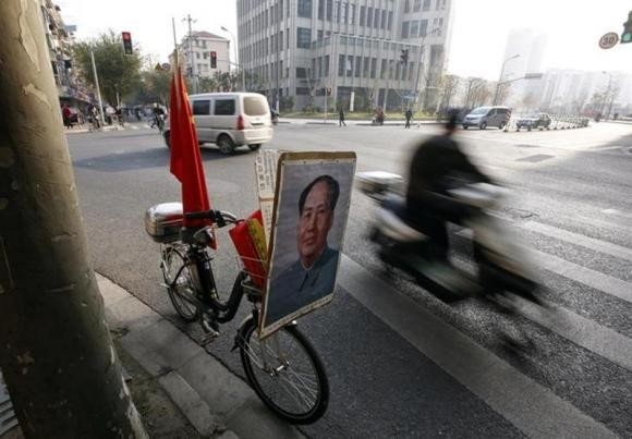 A resident rides past a bicycle bearing a portrait of China's late Chairman Mao Zedong