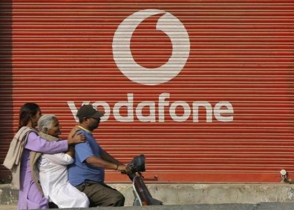 A man and two passengers ride on a scooter past a shop displaying the Vodafone logo on its shutter in Jammu