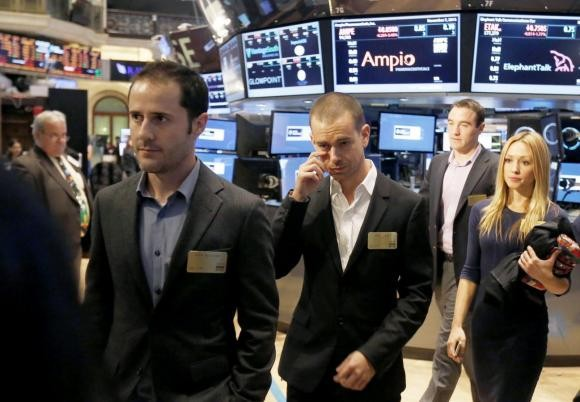 Twitter co-founders Evan Williams (L) and Jack Dorsey (C) walk together during the Twitter Inc. IPO on the floor of the New York Stock Exchange in New York, November 7, 2013.