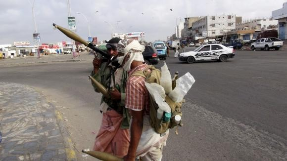 Militia men secure a street leading to the airport during clashes in Yemen's southern port city of Aden March 19, 2015