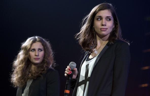 Russian punk band Pussy Riot members Maria Alyokhina (L) and Nadezhda Tolokonnikova speak on stage during Amnesty International's