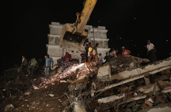 Rescue workers use a cutting tool to search for survivors after a residential building collapsed in Thane, on the outskirts of Mumbai April 4, 2013.