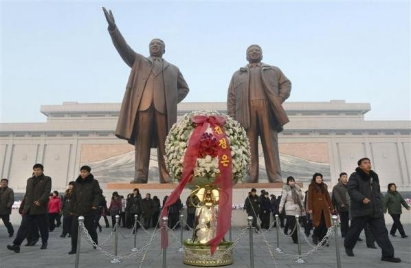 North Koreans offer flowers to bronze statues of North Korea's late founder Kim Il Sung and late leader Kim Jong Il (R) at Mansudae in Pyongyang, in this picture taken and provided by Kyodo December 17, 2013, to mark the second death anniversary of Kim Jong Il.