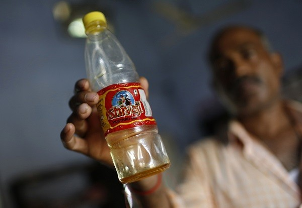 A policeman in civilian clothes shows a bottle containing oil which they recovered from the school where contaminated meals were served to children on 16 July, at a police station in Masrakh at Chapra district of the eastern Indian state of Bihar.